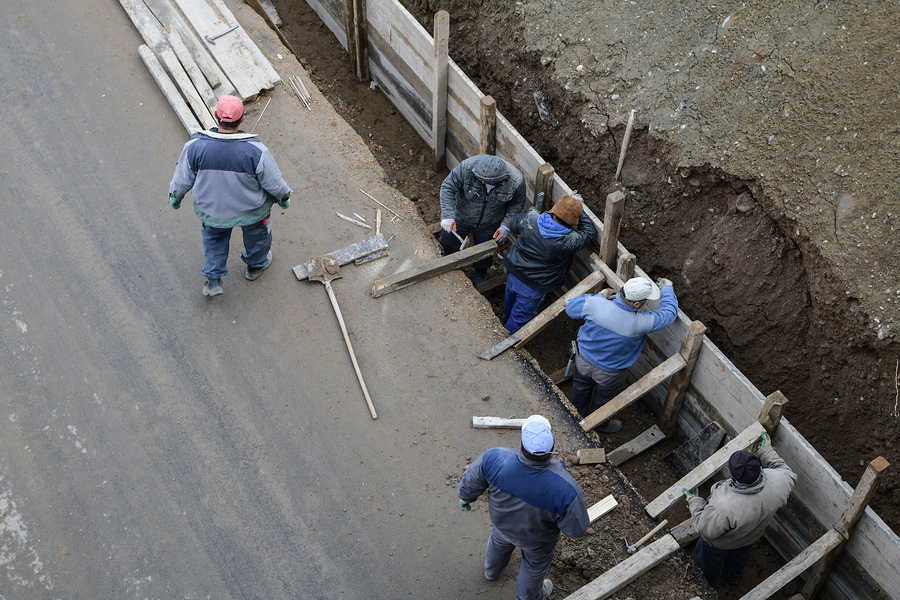 manual workers build the foundation of the bridge on the road
